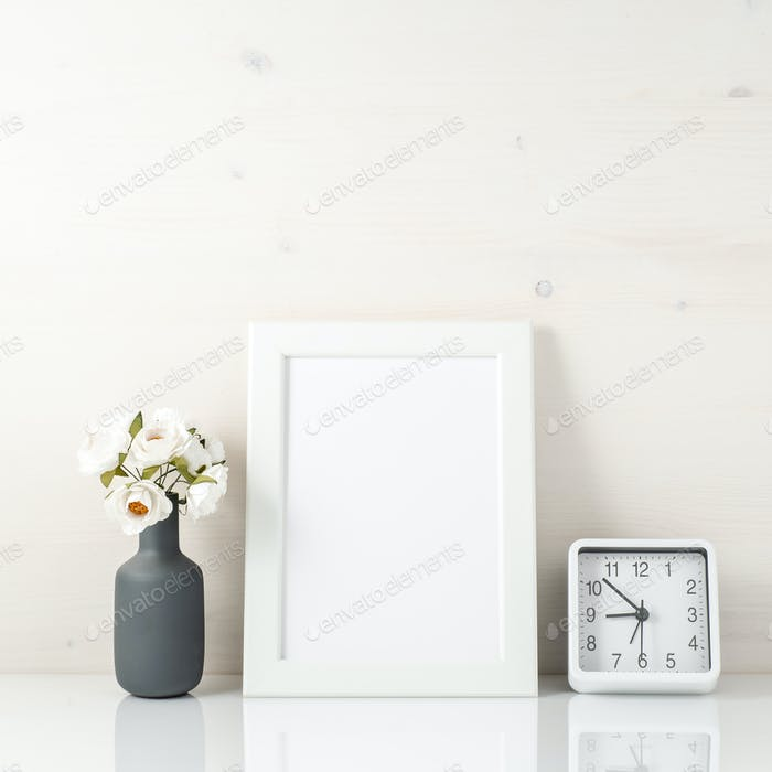 White frame, flower in vase, clock on white table against the wh