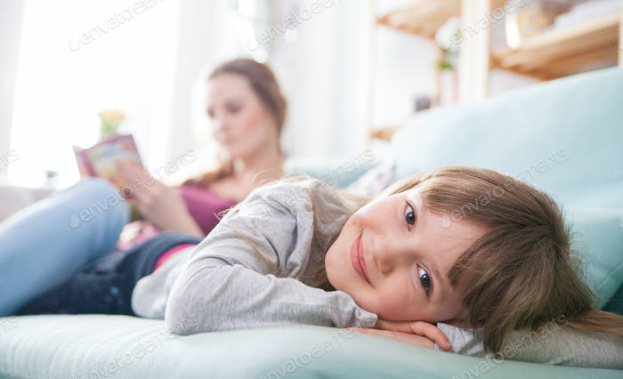 Mother and daughter sitting on sofa and reading book