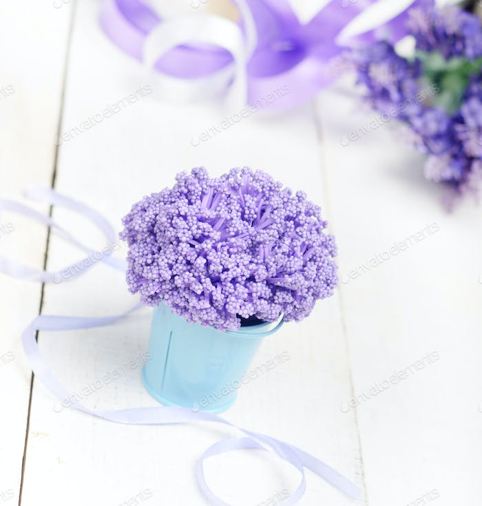 Violet flowers in blue metal bucket on white wooden table