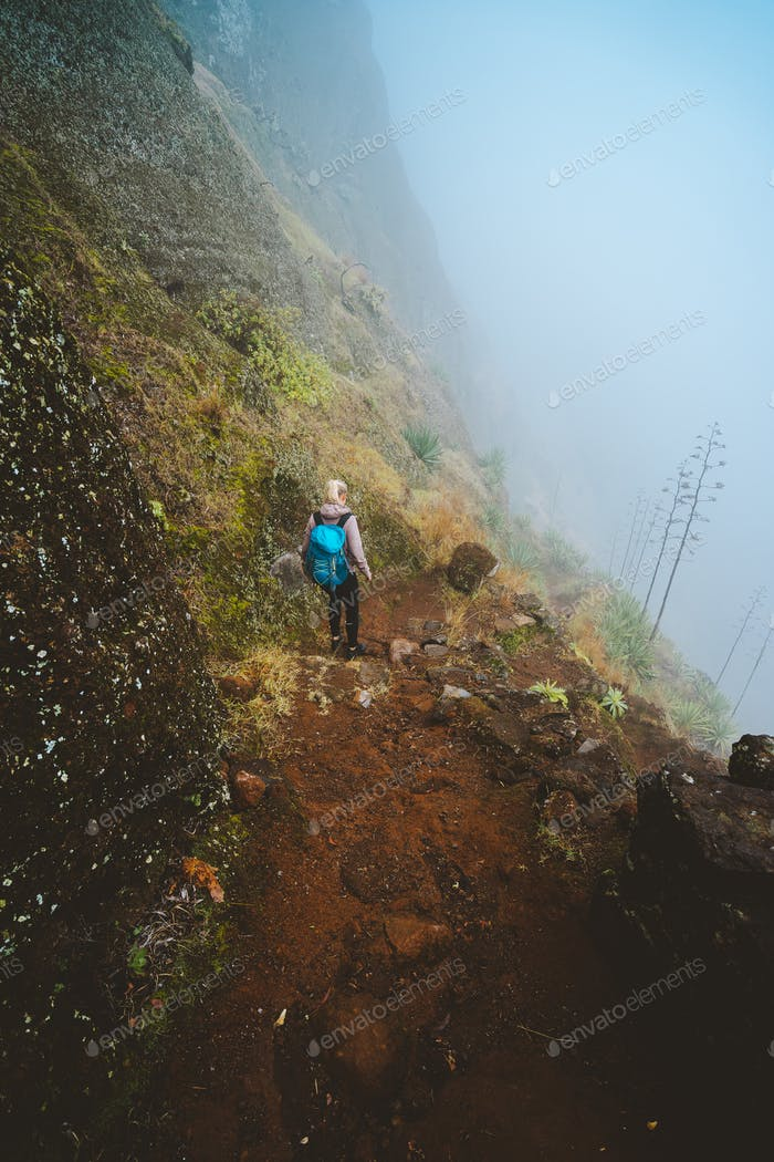 Hiker women with backpack walking down the trekking path. The steep arid slope of the rock. The fog
