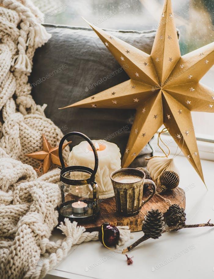 Weihnachtskomposition mit Kaffee, Kerzen und dekorativen Spielzeug auf Fensterbank