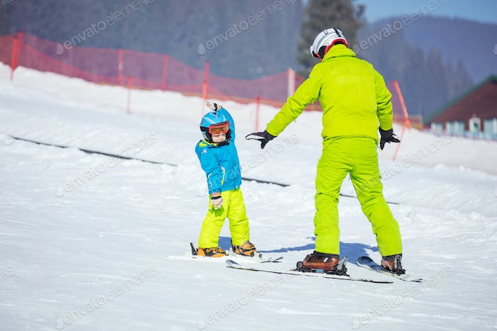 Lesson at skiing school: instructor teaching little skier