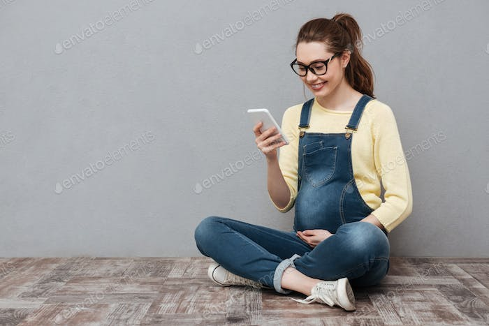 Pregnant cheerful woman using mobile phone.