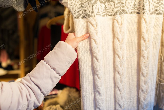 woman buying woolen clothes at christmas market