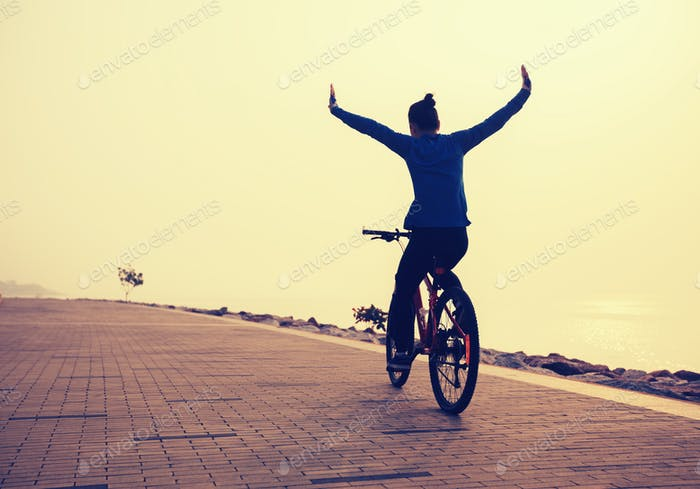 free woman cyclist outstretched arms on sunrise seaside