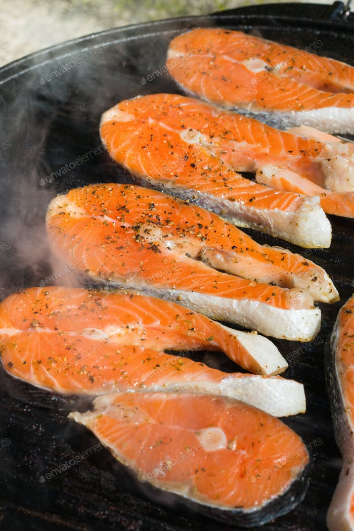 Raw fish salmon steaks on a barbecue, grilling pan