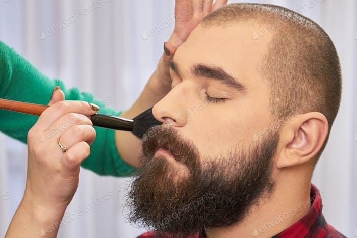 Brush applying makeup, male model