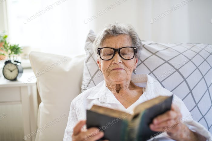 Sick senior woman with glasses reading bible in bed at home or in hospital.