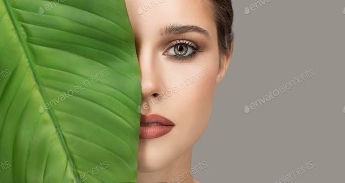 porträt von frau und grünes blatt. Bio Schönheit.