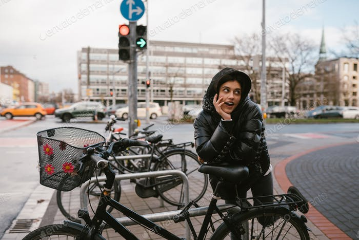 Young woman posing in a parking lot with bicycles