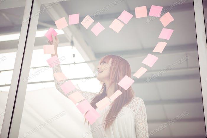 Lächelnde Hipster Frau tun ein Herz in post-it im Büro