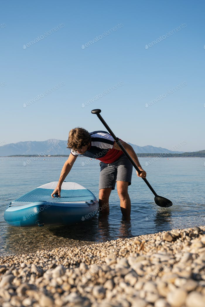 Low angle view of young man taking his sup board out of the water