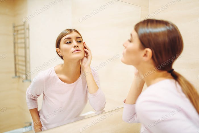 Woman looking on face at the mirror in bathroom