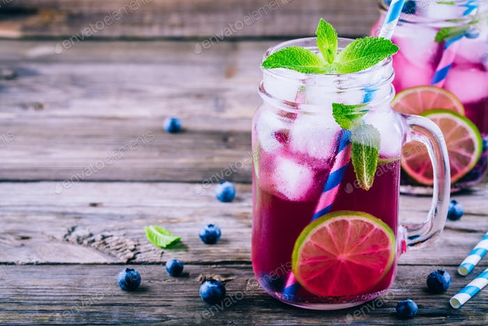 Blueberry ice mojito with lime and mint in mason jar