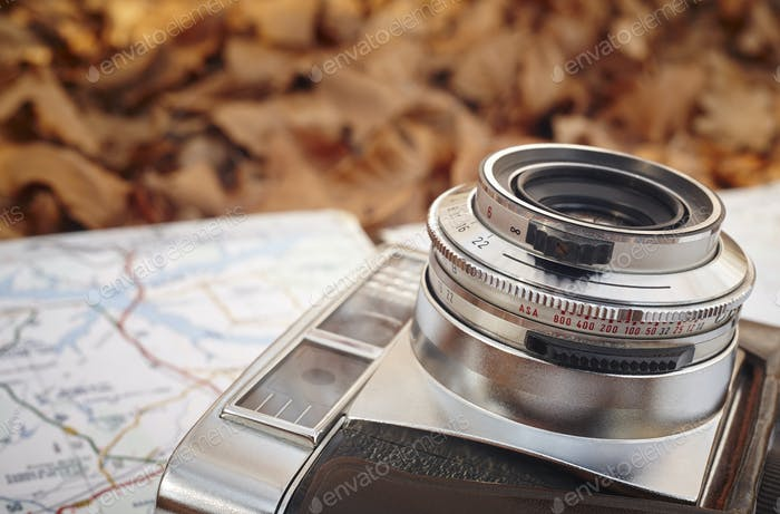 Still life in the autumn forest with camera and map. Horizontal