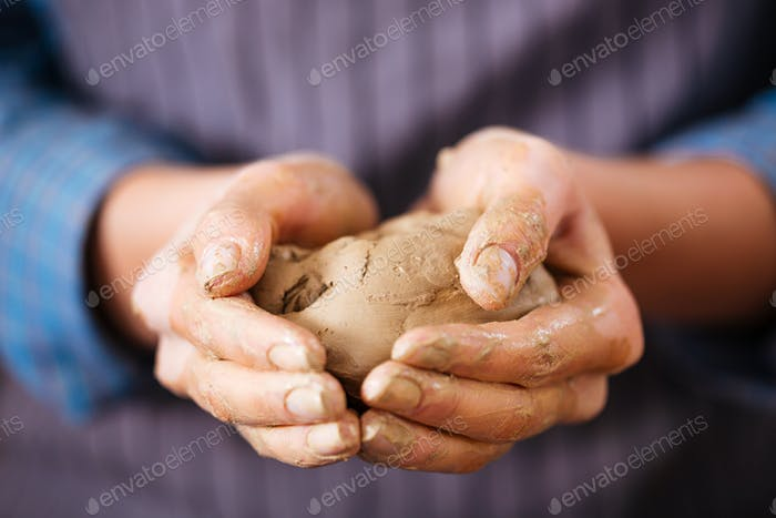 Young woman potter hands holding piece of clay