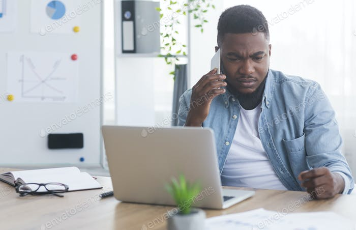 Depressed african american businessman receiving bad news on the phone