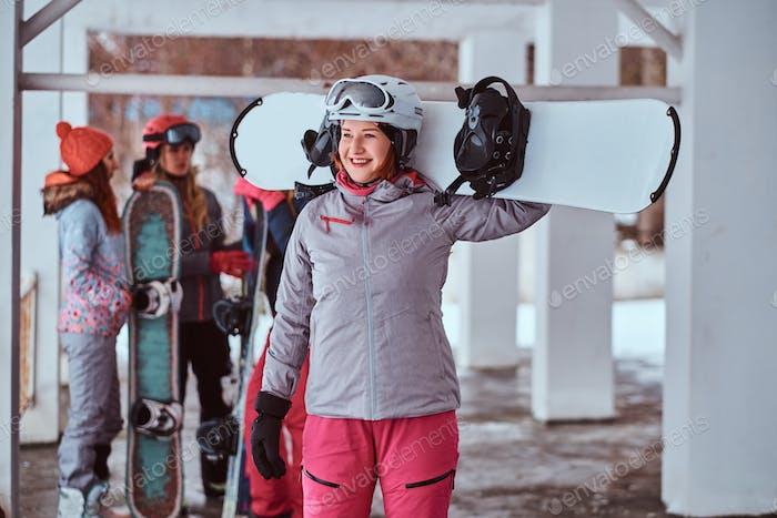 Rothaarige Frau trägt Wintersportbekleidung posiert mit einem Snowboard