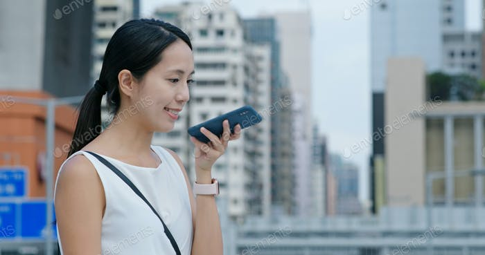 Woman speak to cellphone in city