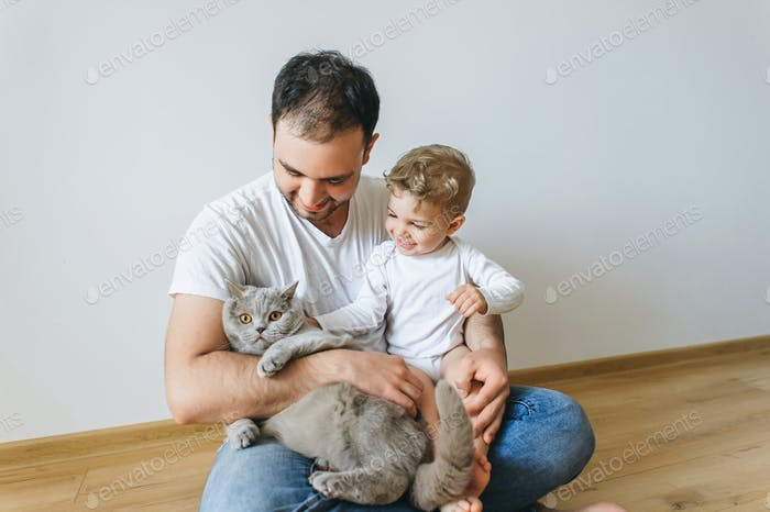 smiling father holding little son in bodysuit and grey british shorthair cat in hands at home