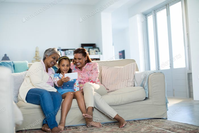 Happy family using digital tablet in living room
