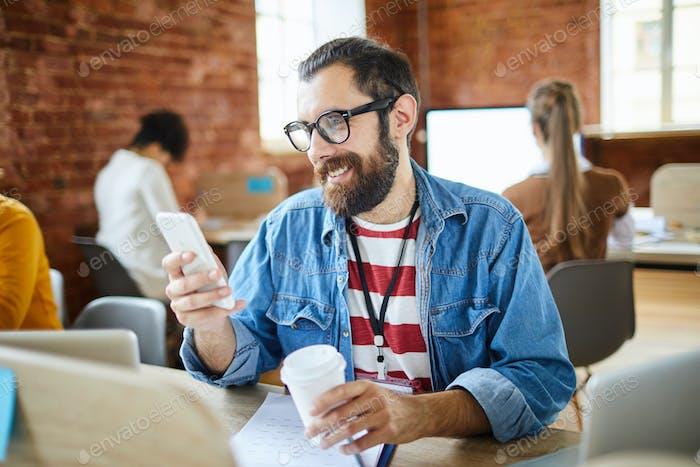 Businessman scrolling in smartphone