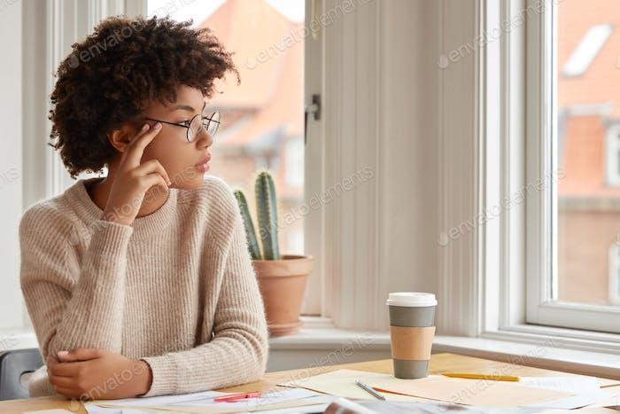 Foto einer kontemplativen Frau mit Afro-Frisur, trägt runde Brille, lässig warmer Pullover, denke