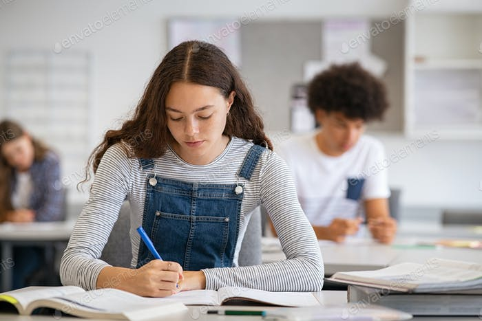College girl studying with concentration in class