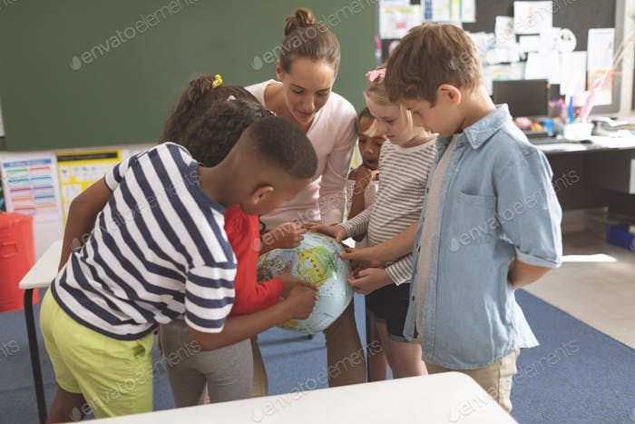 Front view of a schoolteacher explaining to his school kids the earth globe in classroom at school