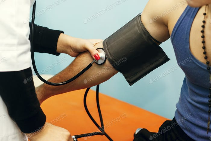 Professional nurse measuring pressure for strong handsome man hand closeup