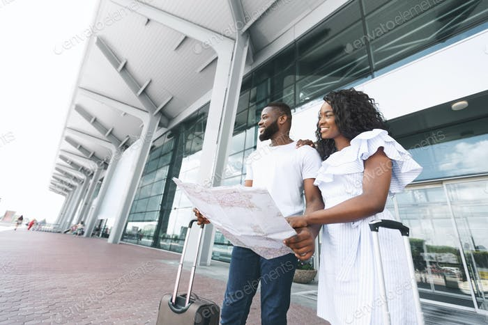 African couple searching places to visit, using map at airport