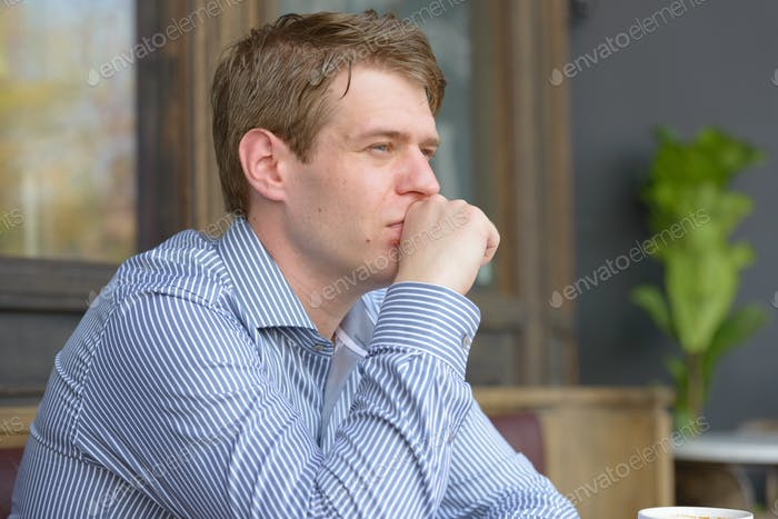 Face of young handsome blond businessman thinking at the coffee shop