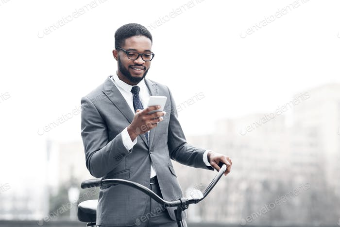Afro businessman texting on phone, standing with bicycle