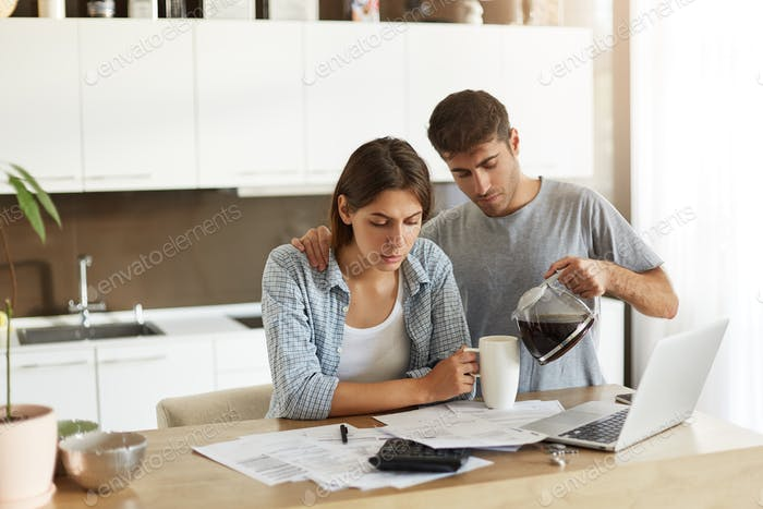 Domestic finances, home accounting, taxes, money and financial problems concept. Worried young Ameri