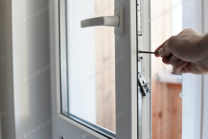 Man's hand uses screwdriver for adjustment of hardware of the uPVC door mechanism.