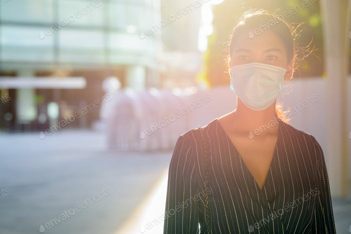 Young Asian businesswoman with mask for protection from corona virus outbreak in the city outdoors