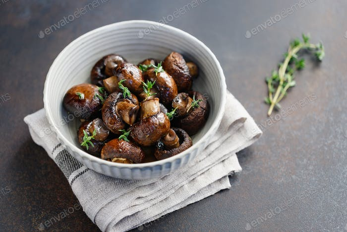 Roasted champignons with thyme in a ceramic bowl. Simple taste recipe.