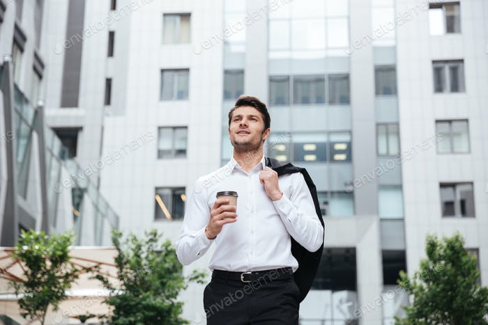 Businessman walking and drinking take away coffee outdoors