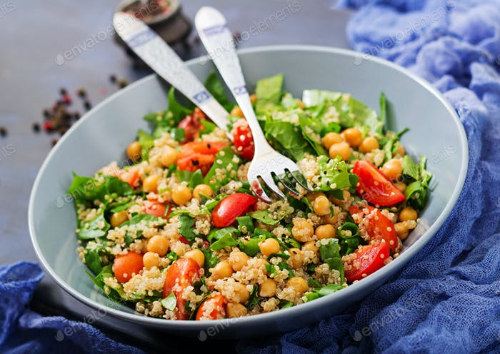 Healthy vegan salad of fresh vegetables - tomatoes, chickpeas, spinach and quinoa