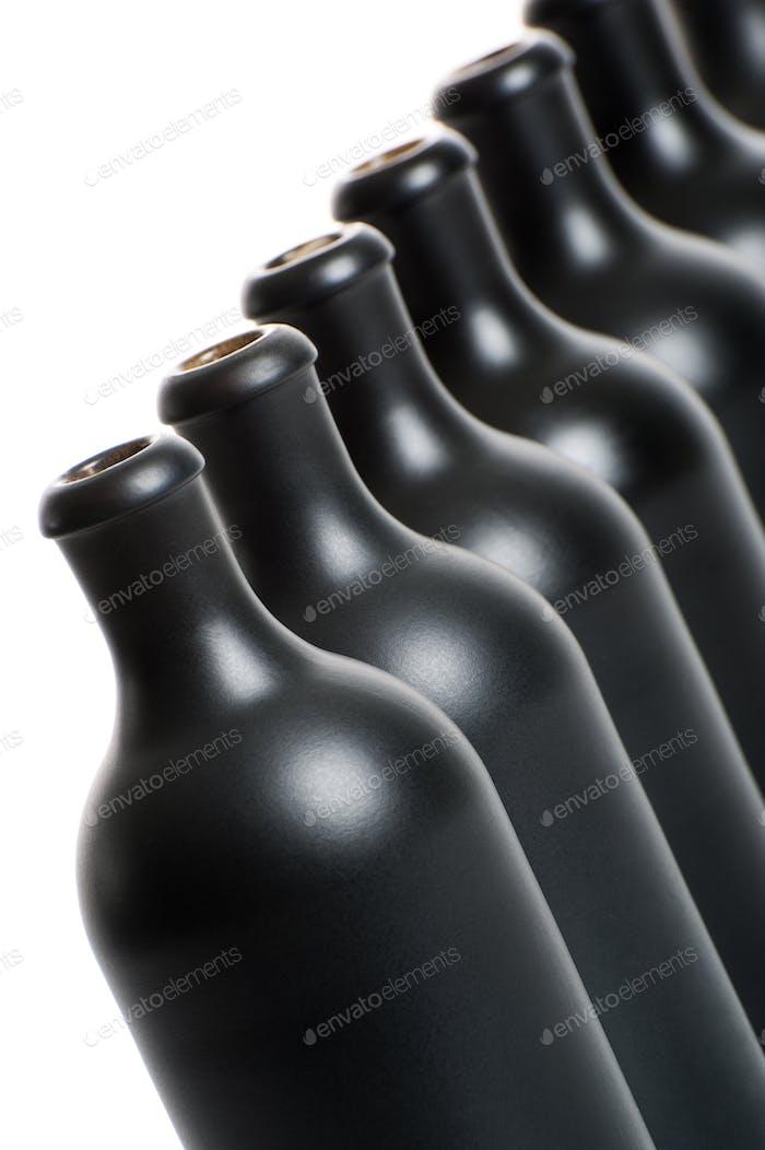 A set of several matte black bottles on a white background close
