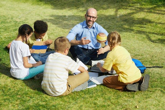 Group of Children Enjoying Astronomy Lesson Outdoors