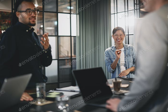 Asian businesswoman smiling during a presentation with diverse colleagues