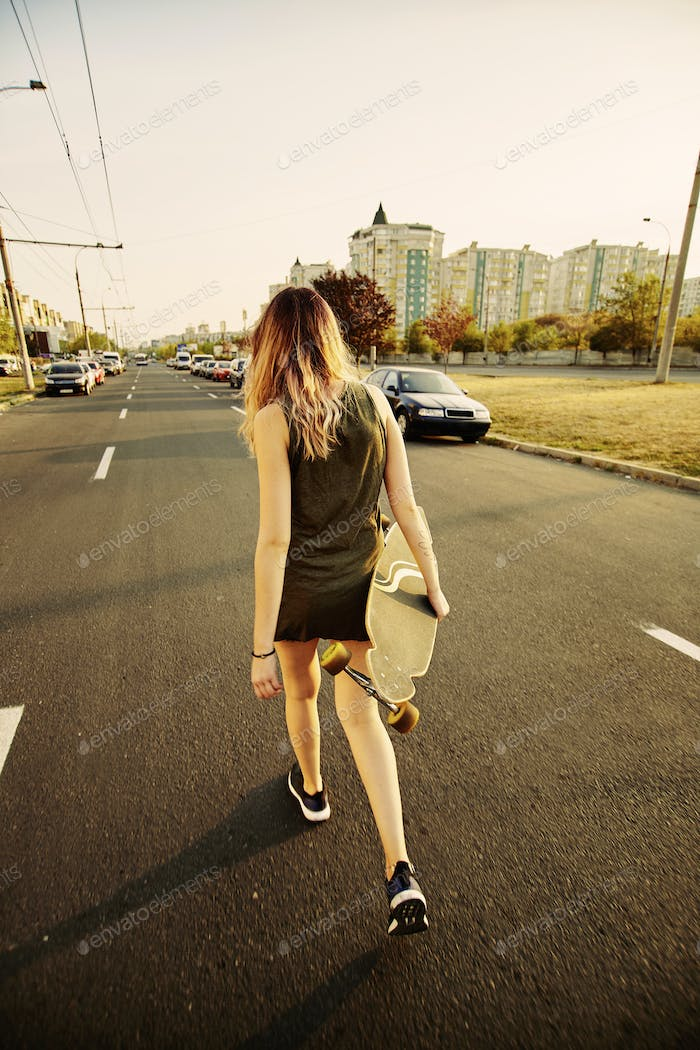 Beautiful young tattooed girl with longboard in sunny weather