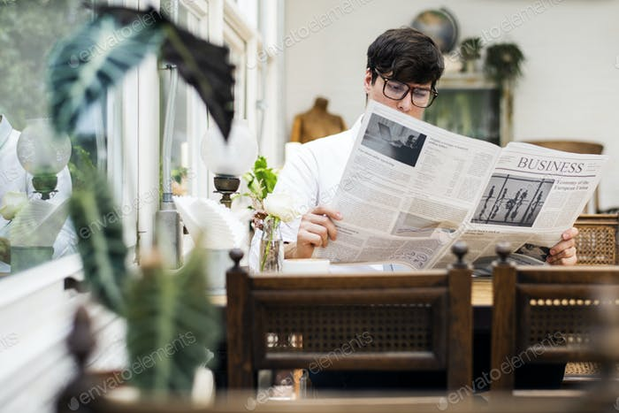 Young man reading newspaper in the morning
