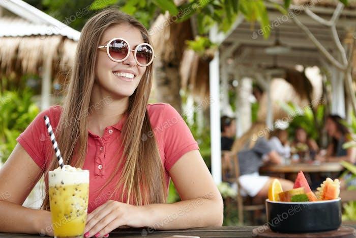Tourismus und Urlaub. Schöne junge kaukasische Dame sitzt mit einem Glas Smoothie an der Theke