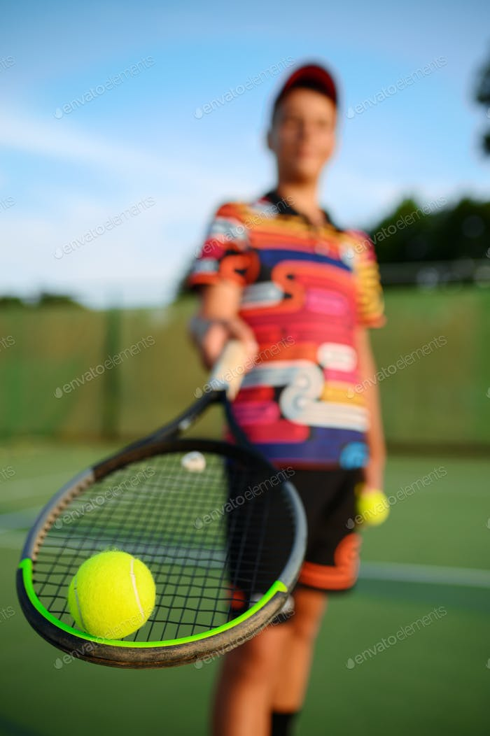 Male tennis player poses with racket and ball