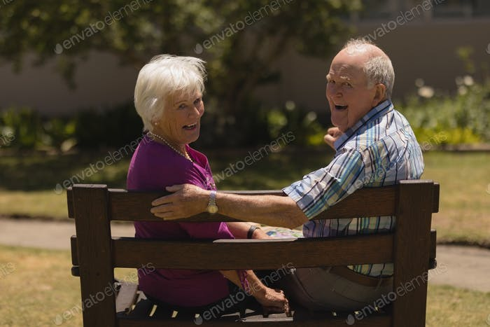 Senior couple sitting together on the bench and smilling at the camera