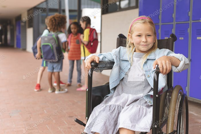 Schoolgirl sitting on wheelchair in corridor against school kids speaking together