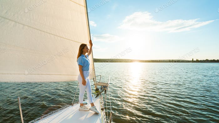 Young Woman Standing On Yacht Deck Enjoying Ride Outdoors