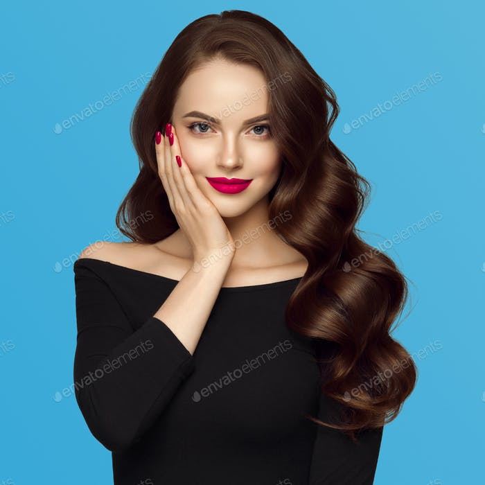 Beautiful hair woman with long brunette hair beauty healthy hairstyle. Blue background. With hands.